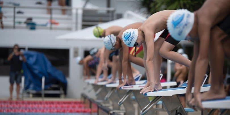 Age group swimmers on starting blocks