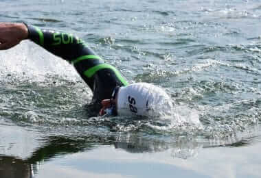 Swimmer with wetsuit in cold water