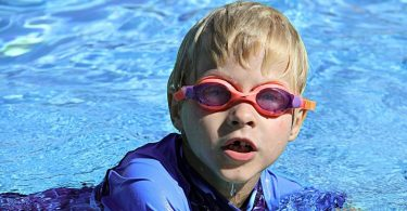 Toddler swimming with goggles