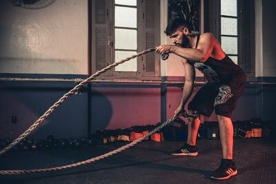 swimmer training with battle ropes